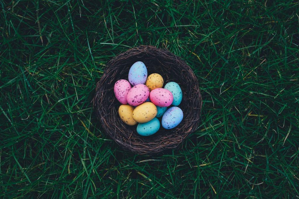 Ovos coloridos dentro de uma cestinha marrom.