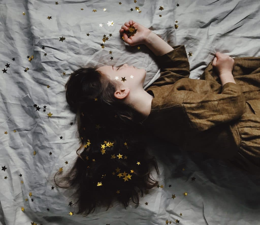 Criança deitada dormindo na cama com estrelas jogadas ao redor e cabelo solto