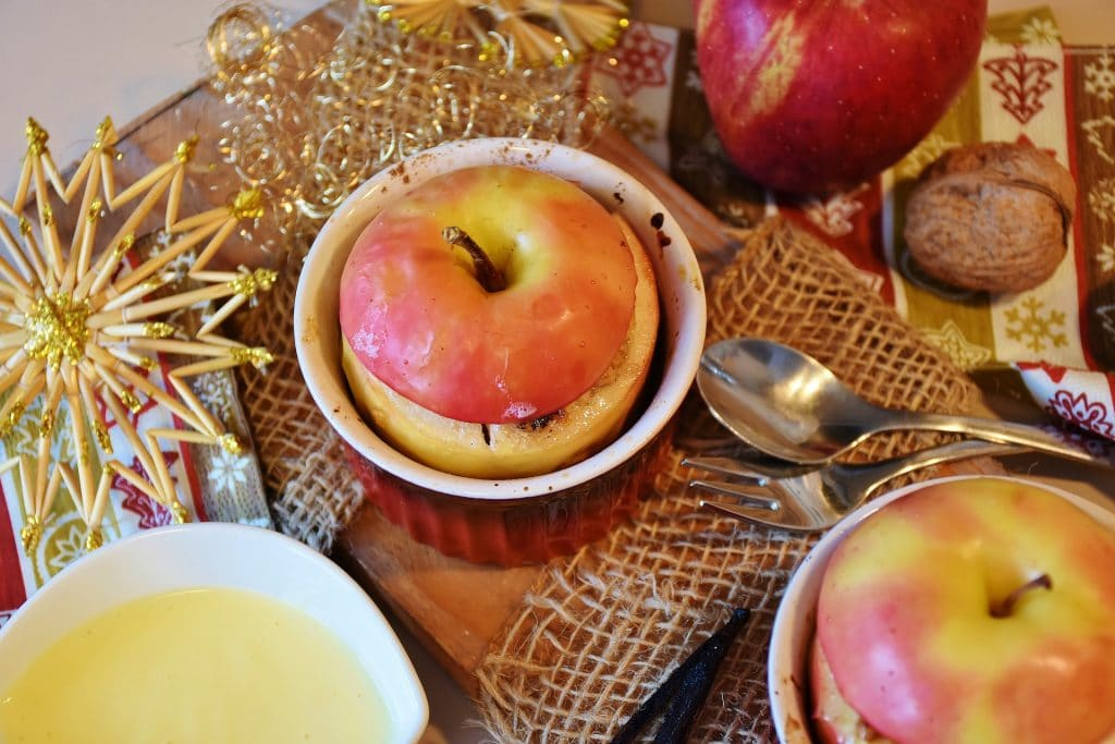 Sobremesa de maçã cozida feita com mel e castanhas servidas em potes de porcelana na cor vermelha servida sobre uma mesa decorada com enfeites natalinos.