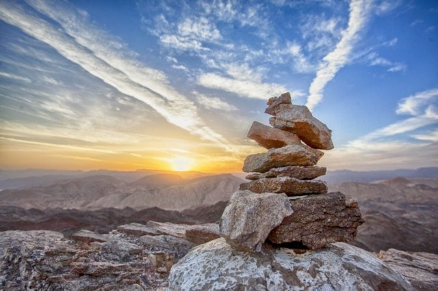 Conjunto de pedras vistas de cima com pôr-do-sol e e céu azul ao fundo