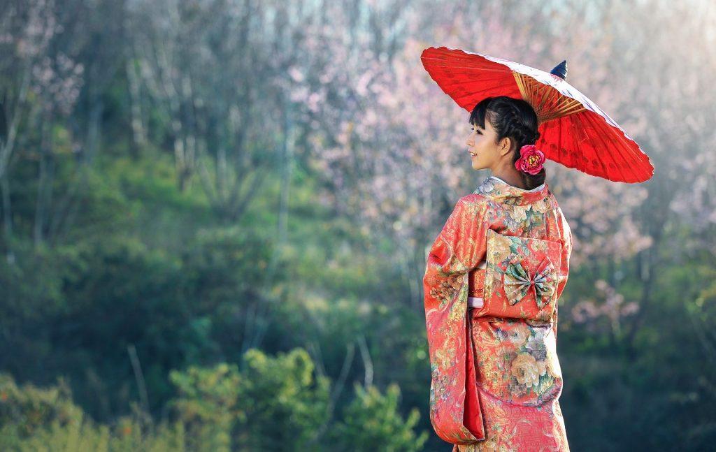 Imagem de uma linda japonesa usando uma sombrinha e um lindo kimono vermelho estampado com muitas flores. Ela está obserando uma linda floresta.