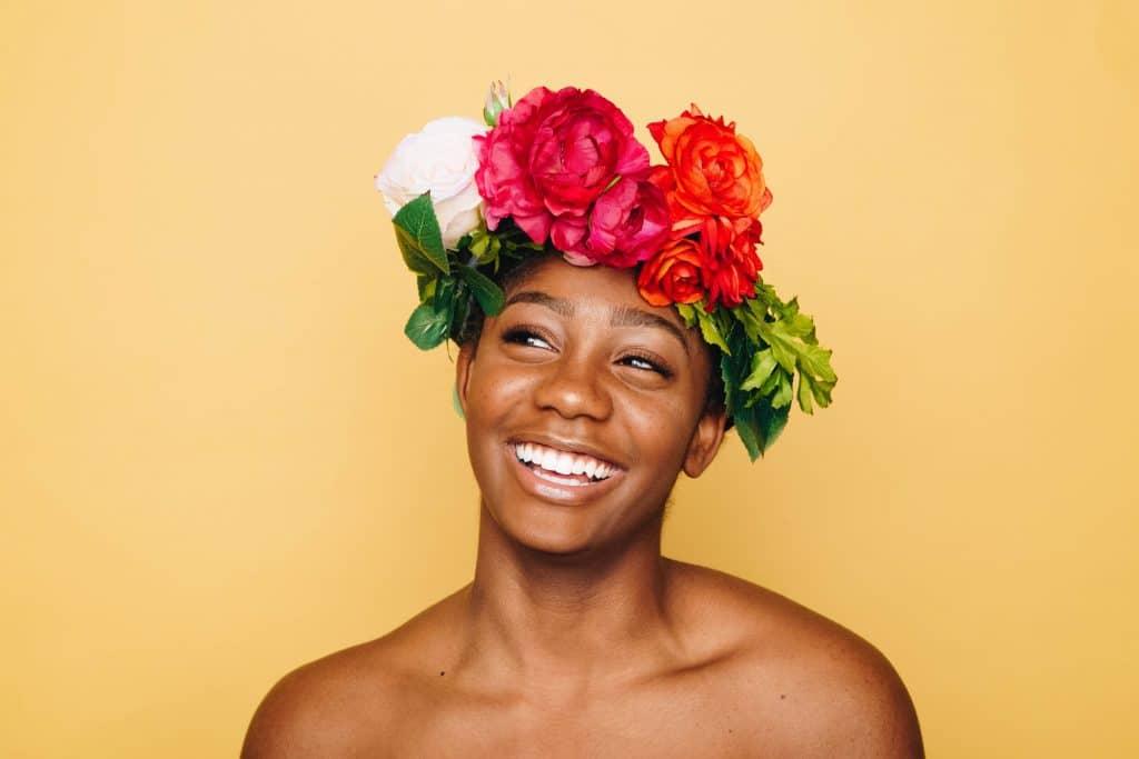 Mulher sorridente com uma coroa de flores sobre a cabeça, olhando para o lado.