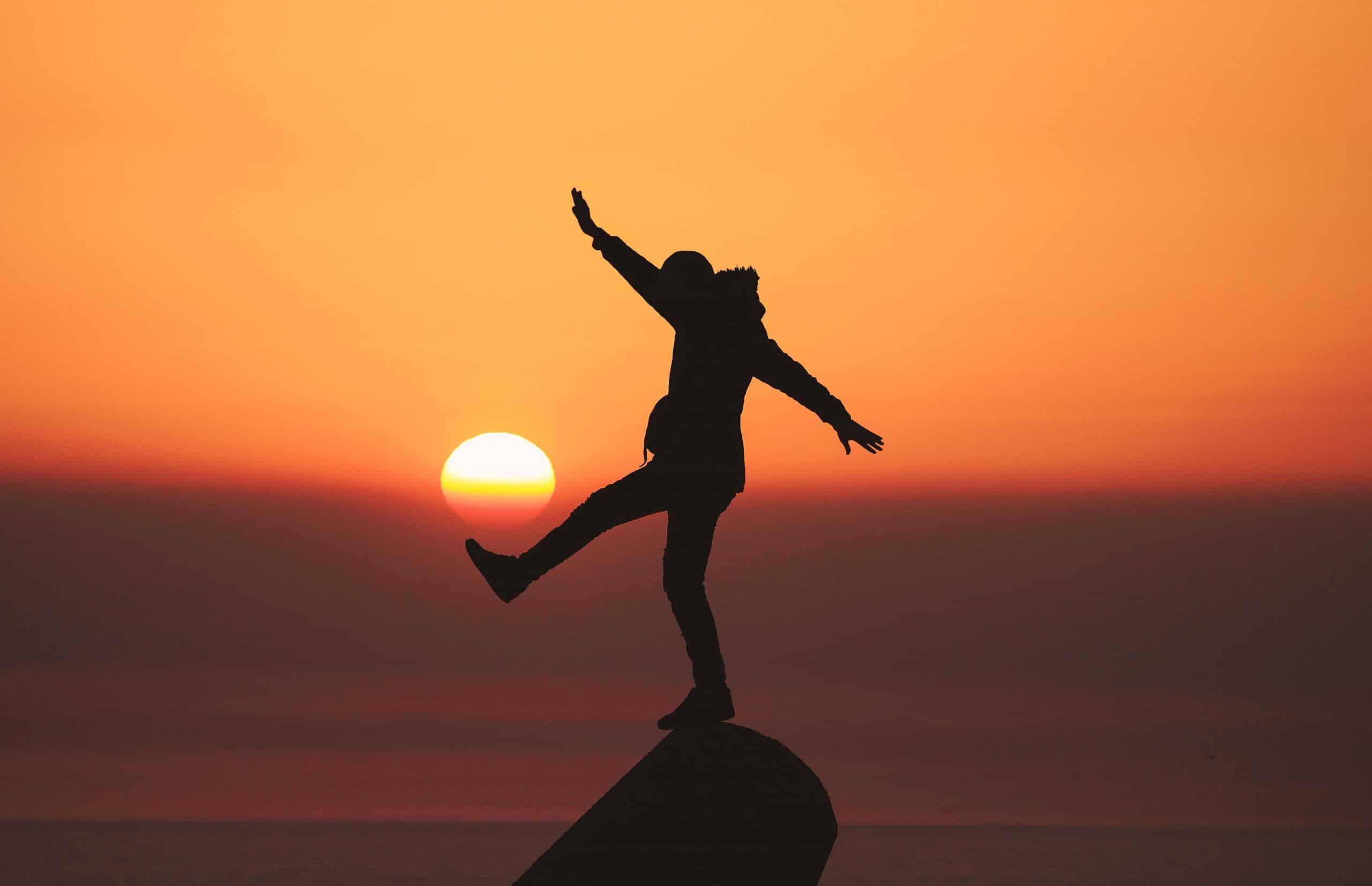 Silhueta de um homem em pé em um lugar alto, à frente de uma paisagem com pôr do sol. O homem tem seus braços abertos e um dos pés para a frente.