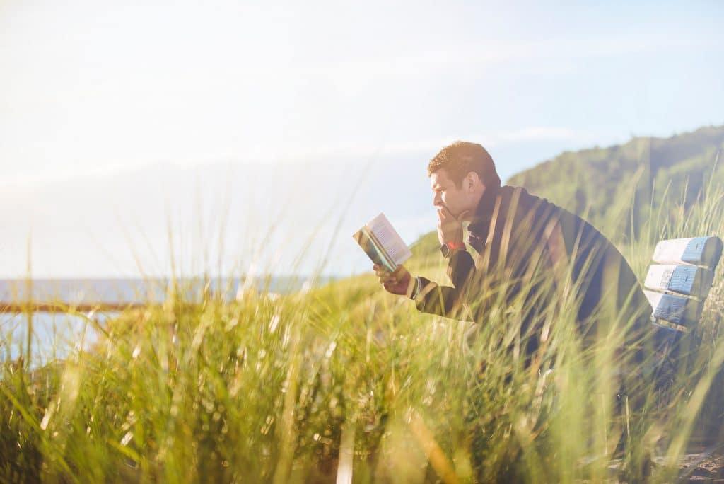 Homem sentado lendo um livro em uma paisagem natural, com um rio ao fundo.