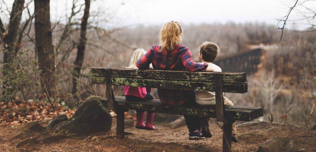 Mulher sentada em banco de madeira, com duas crianças, observando a vista de uma floresta durante o outono.