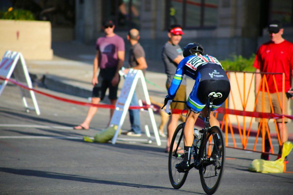 Homem praticando uma corrida de bicicleta. Ele usa roupas apropriadas para a prática desse esporte. Fora da pista de corrida, outros homems observam a corrida.