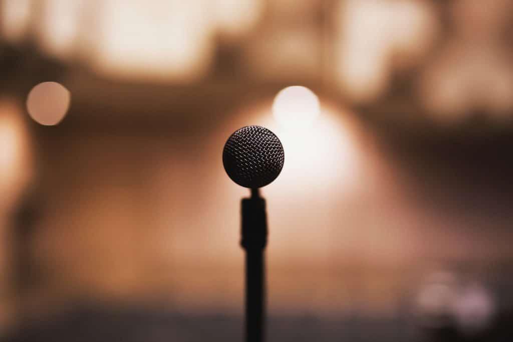 Microfone em pedestal, e fundo desfocado.