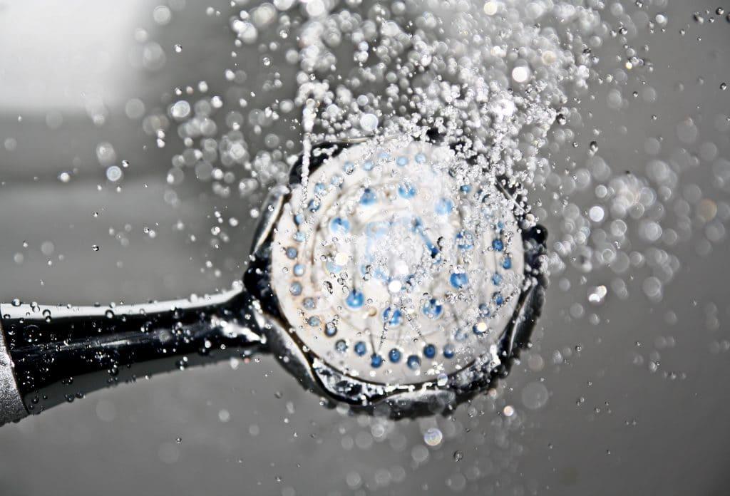 Imagem ampliada de uma ducha de banho ligada, com gotas de água se espalhando.