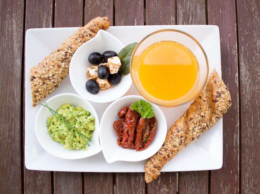 Imagem de um prato com alimentos favoráveis para uma reeducação alimentar. O prato é composto por suco,  salada, frutas e pão integral.