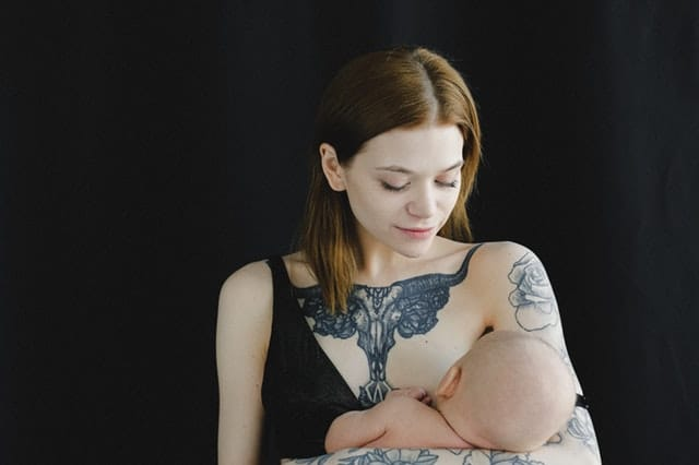 Mulher amamentando filho com olhos fechados e com fundo preto
