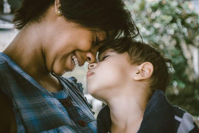 Mãe e filho com rostos encostados pelo nariz sorrindo de olhos fechados