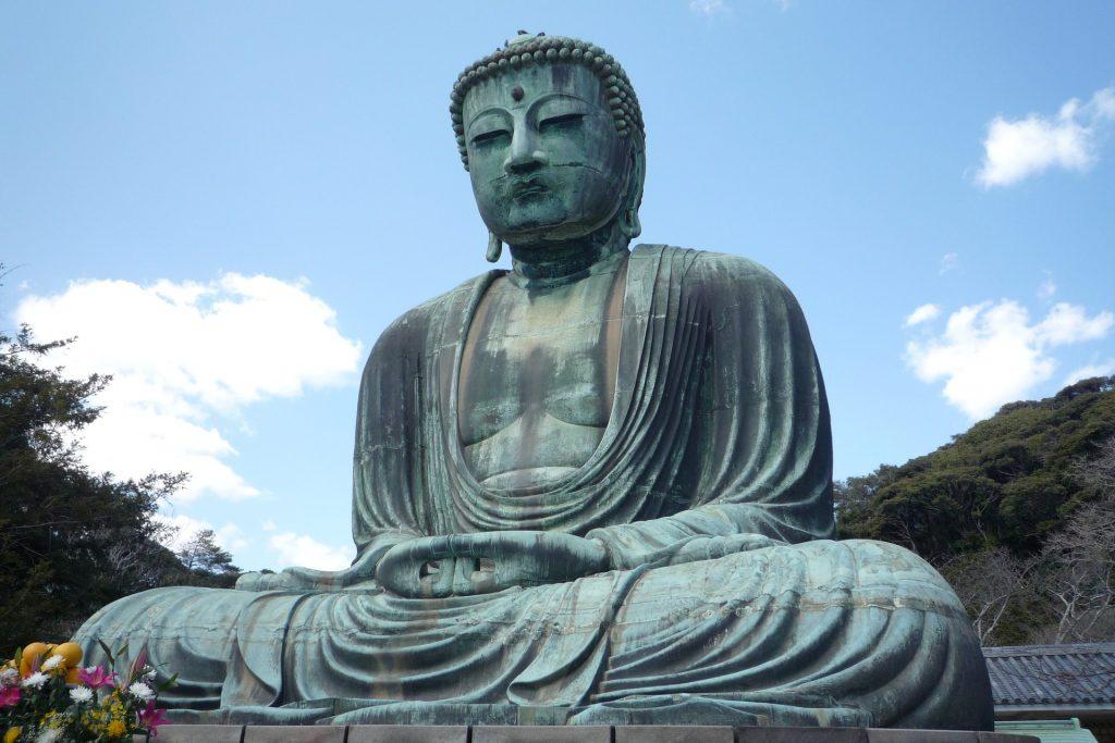 Linda imagem de uma estátua gigante de Buda em posição de meditação. Ao lado da estátua, vários arranjos de flores entregues como oferendas.