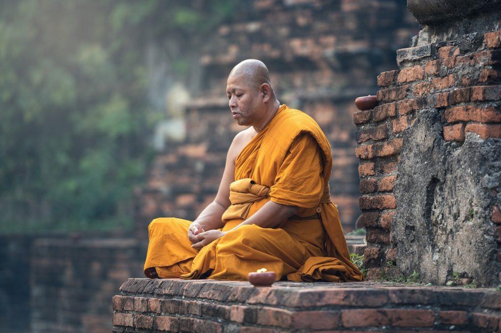 Imagem de um monge budista fazendo uma sessão de meditação. Ele esta sentado sobre uma montanha de pedras e veste uma túnica amarela.