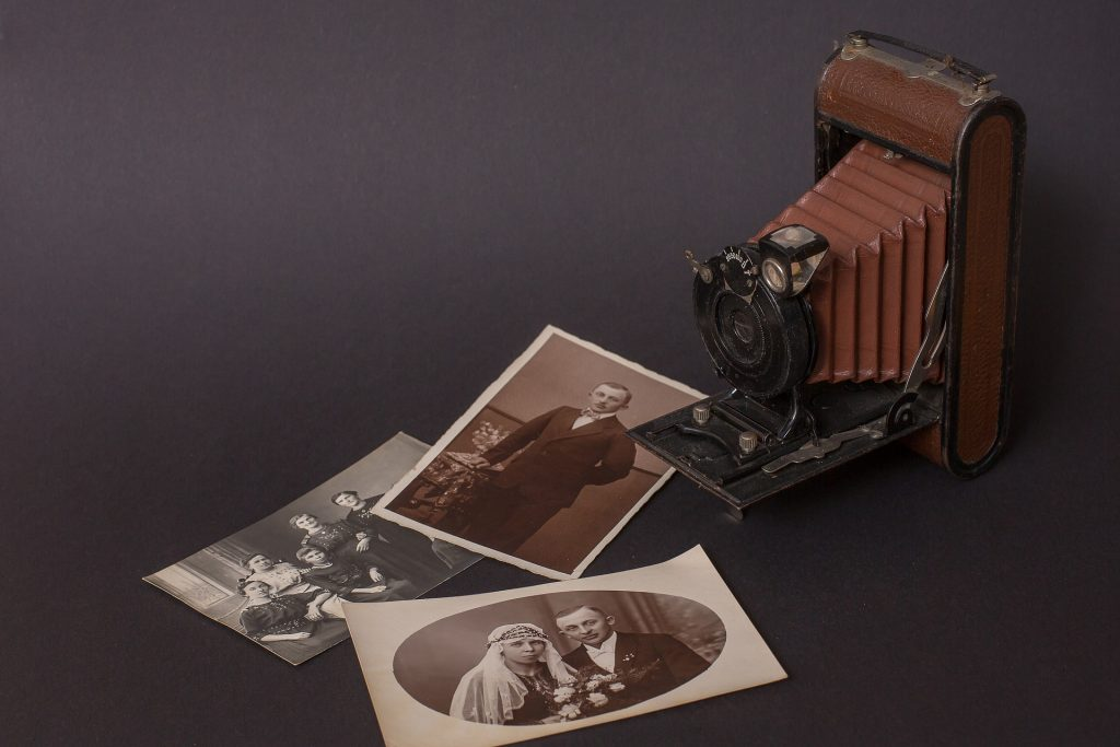 Imagem de uma câmera fotogrática antiga e bem nostálgica. Ela está sobre uma mesa com fundo preto e algumas fotos antigas de pessoas também estão espalhadas sobre a mesa.