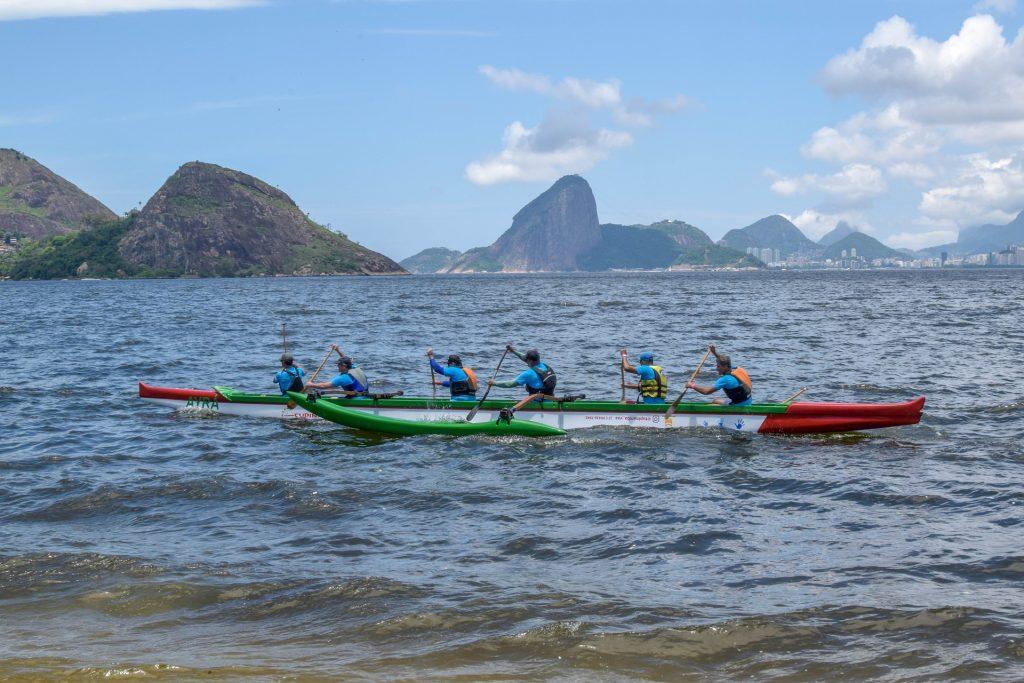 Grupo de homens vestindo coletes praticando canoagem em um lago na cidade do Rio de Janeiro.