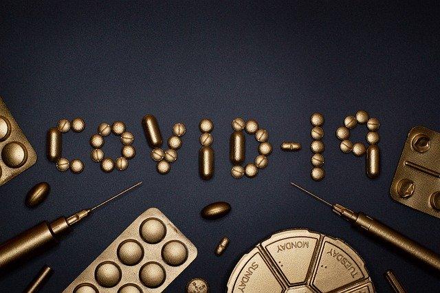 """Comprimidos dourados escrevem """"COVID-19"""" enquanto seringas e cartelas de comprimidos dourados estão espalhados na parte de baixo da imagem."""