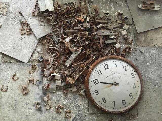 Relógio de parede quebrado, caído no chão, cheio de entulho metálico em volta.
