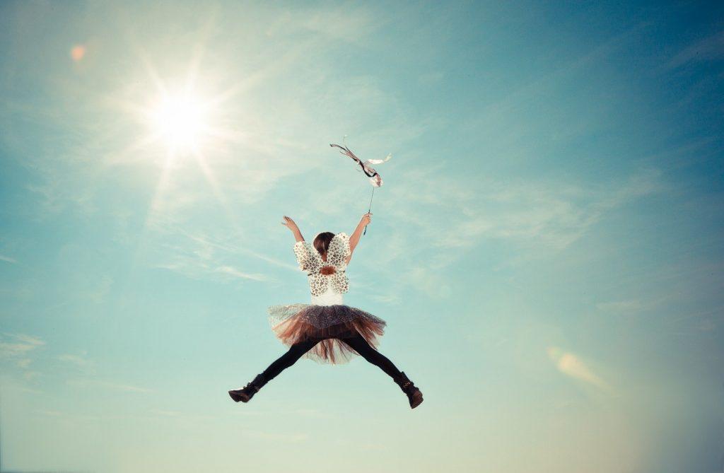 Criança vestida de fada pulando até o céu