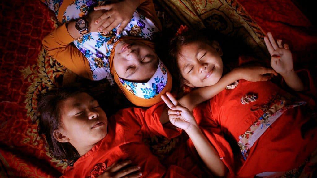 Três meninas deitadas de olhos fechados como se estivessem dormindo.