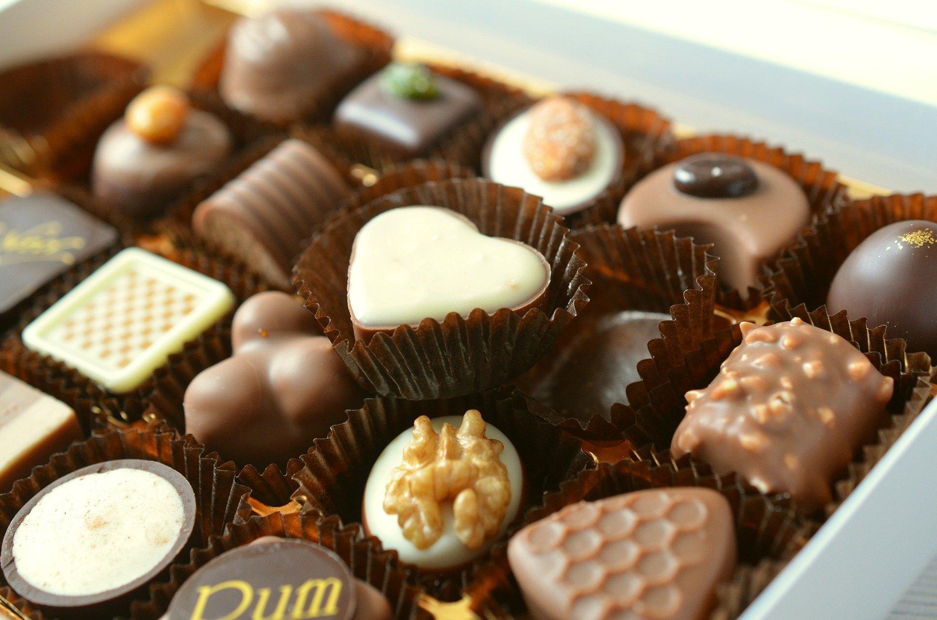 Imagem de uma caixa cheia de bombons de chocolate branco, ao leito, amargo e meio amargo, feitos de várias formatos e sabores diferenciados.