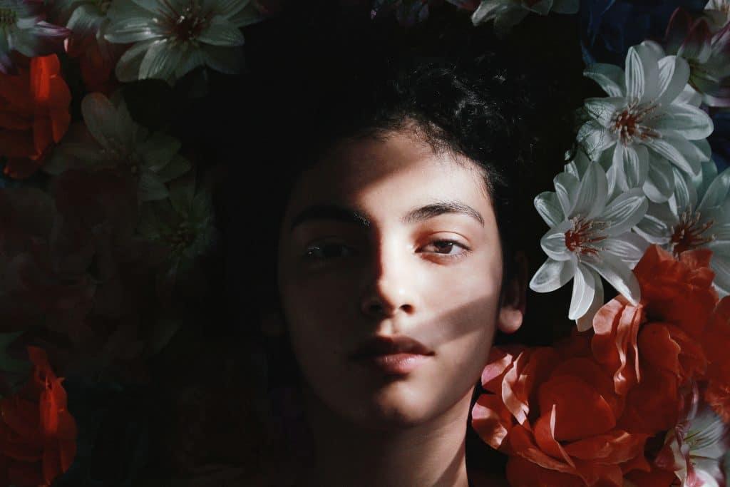 Mulher de cabelos longos deitada, cercada por flores.