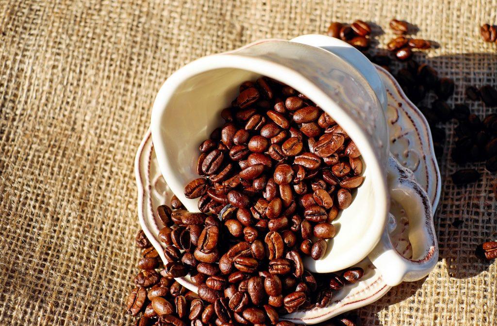 Imagem de um lindo conjunto de xícara e pires em porcelana. A xícara está cheia de grãos de café. O conjunto está sobre uma mesa forrada com um tecido de juta.