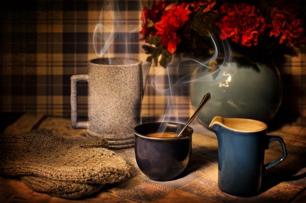 Imagem de uma mesa decorada com juta. Sobre ela uma caneca de café, um bule e um arranjo de flores vermelhas decoram o espaço.