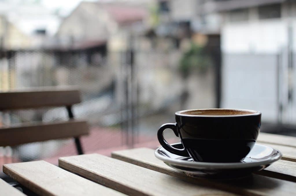 Imagem de uma xícara de café de porcelana na cor marrom. A xícara está disposta sobre uma mesa de madeira.