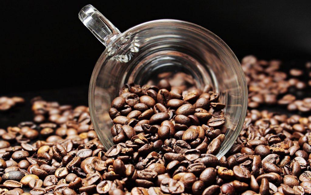 Imagem de grãos de café espalhados sobre uma mesa. Sobre os grãos uma xícara de café de vidro.