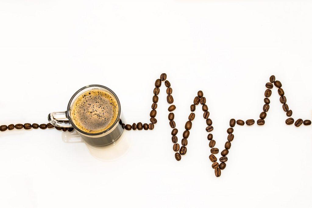 Imagem de grãos de café desenhando um gráfico dos batimentos cardiácos. Sobre esse gráfico uma xícara cheia de café.