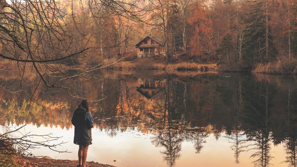 Mulher de costas, em pé, na frente de um lago cercado por árvores de outono, cujas folhas já estão quase todas caídas. Ao fundo, uma pequena casa é vista à beira do lago.