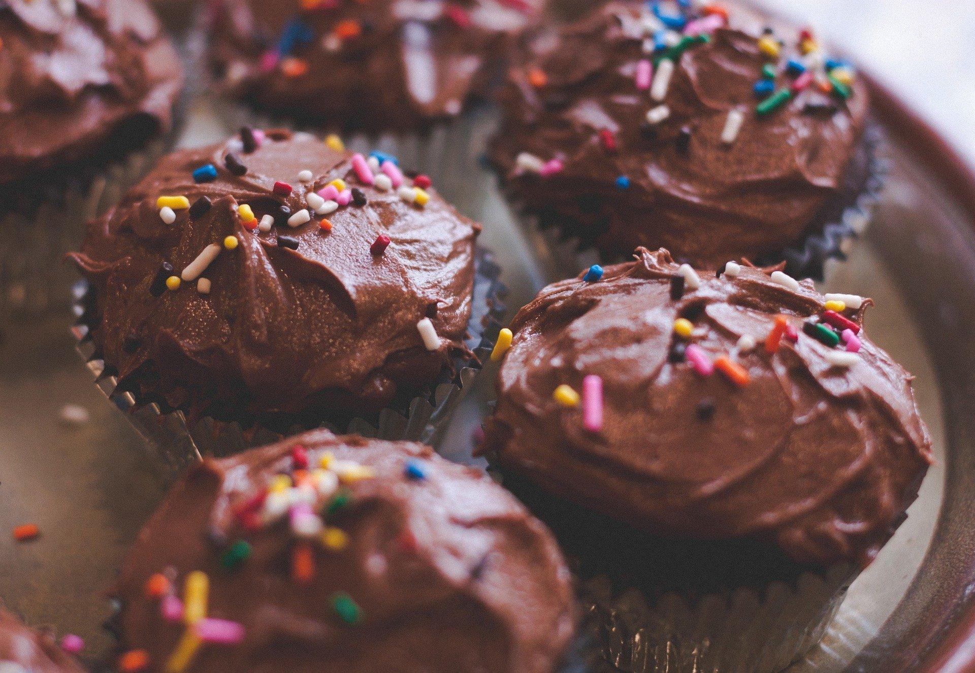 Travessa com cupcakes de chocolate disponíveis em forminhas de alumínio prateado. Eles estão decorados com chocolate granulado colorido.