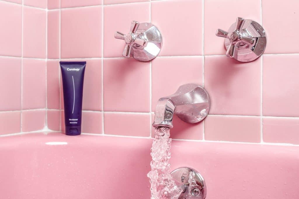 Torneira de uma banheira ligada, com um produto de higiene pessoal na borda.