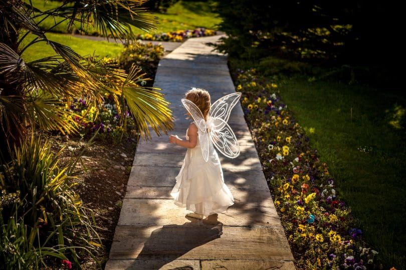 Criança andando em uma passagem de madeira vestida de fada