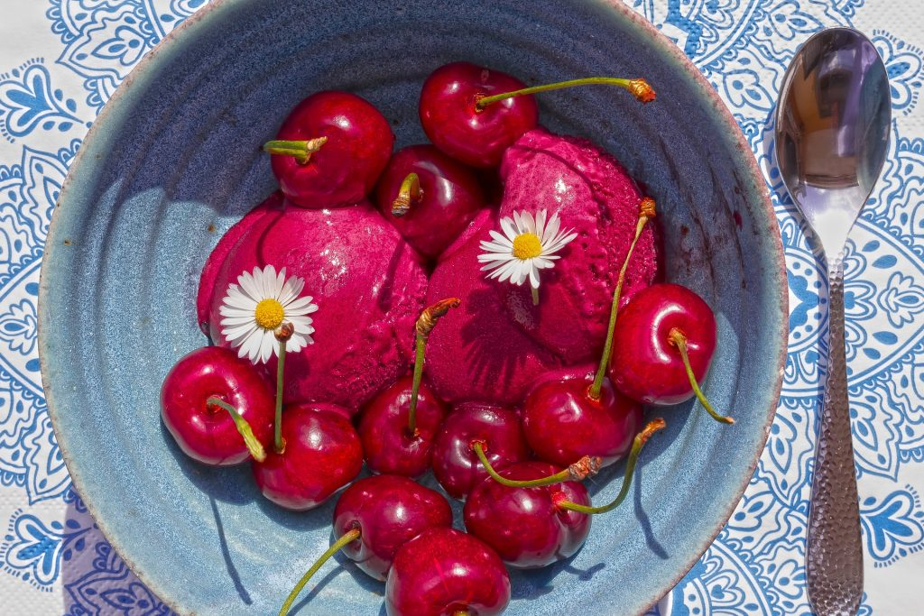 Imagem de um pote azul de cerâmica cheio de sorvete de massa no sabo de vinho. Sobre ele várias cerejas e duas flores de margarida.
