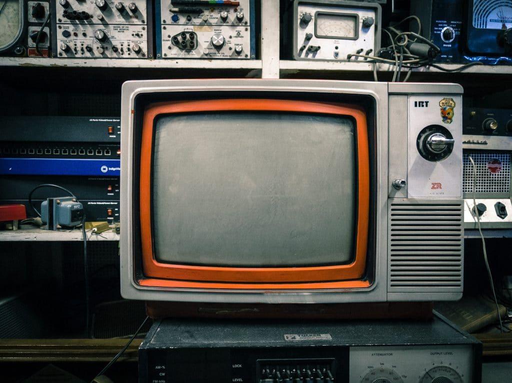 Televisão sendo apoiando em um rádio antigo