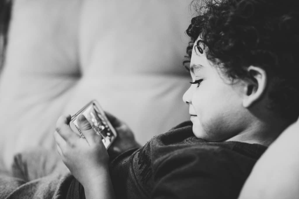 Criança mexendo no celular deitado no sofá da sala