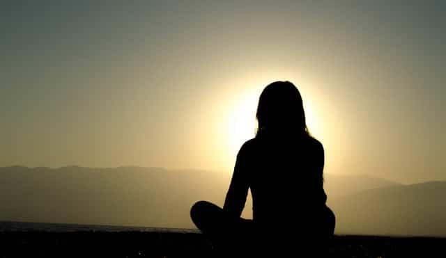 Silhueta de mulher meditando com sol ao fundo
