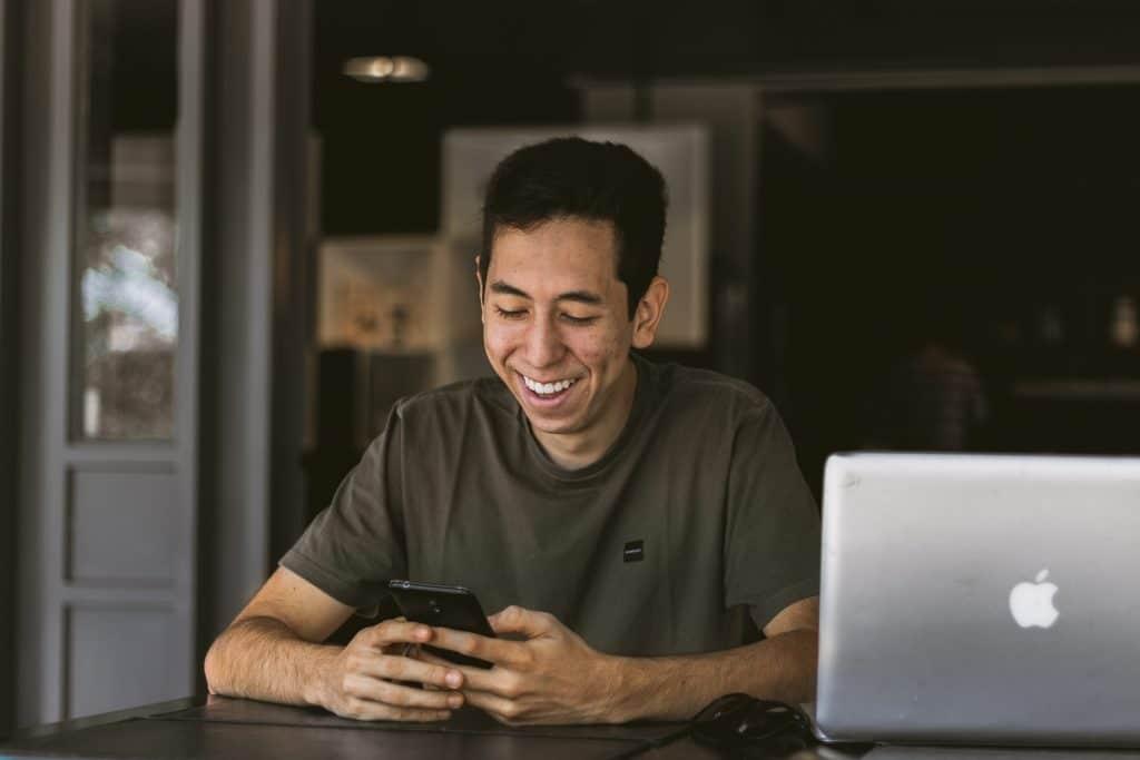 Homem sentado, sorrindo, enquanto usa seu smartphone.