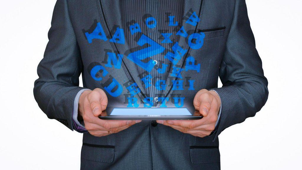 Homem vestindo um terno azul. Ele segura em suas mãos um aparelho eletrônico. Ao fundo imagens de letras do alfabeto em cor azul claro compõem a imagem.
