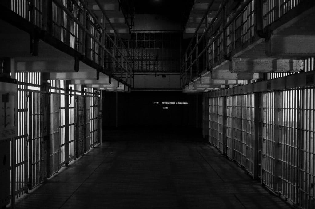 Imagem do corredor de uma cadeia escura, com várias celas vazias.
