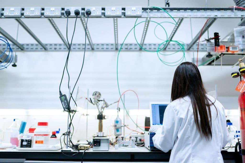 Imagem de um profissional de engenharia (mulher) dentro de uma sala de laboratório  pesquisado e estudando forma de extração do petróleo.