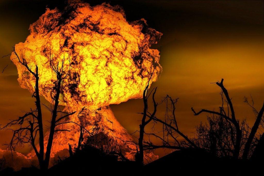 Imagem de uma explosão em formato de bola de fogo no meio de um cerrado.