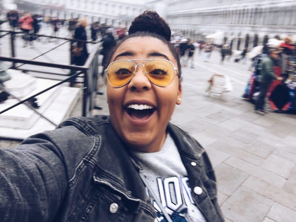 Mulher tirando uma foto de si na cidade e sorrindo