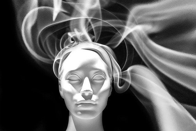Escultura de uma cabeça com olhos fechados, e fumaça saindo dela, indo em diversas direções.