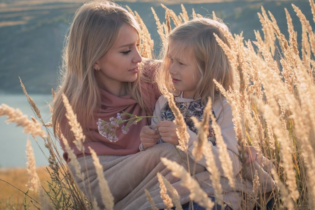 Imagem de mãe e filha em um lindo dia ensolarado. A criança está sentada no colo da mãe que está sentada em um campo com uma plantação de folhagens douradas.