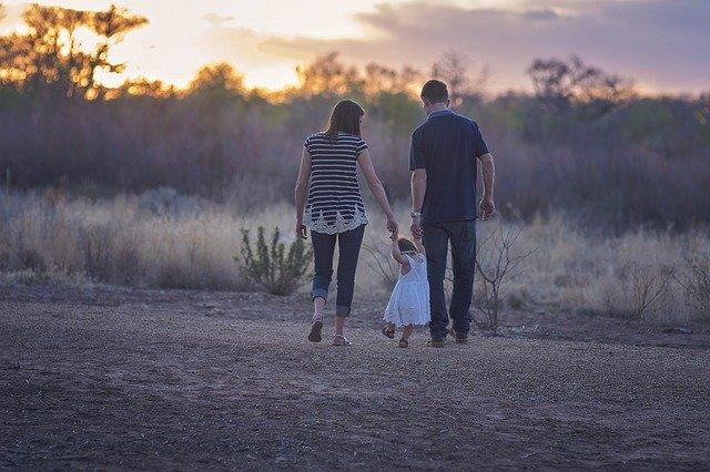 Mãe e pai de mãos dadas com filhinha aprendendo a andar em campo ao entardecer