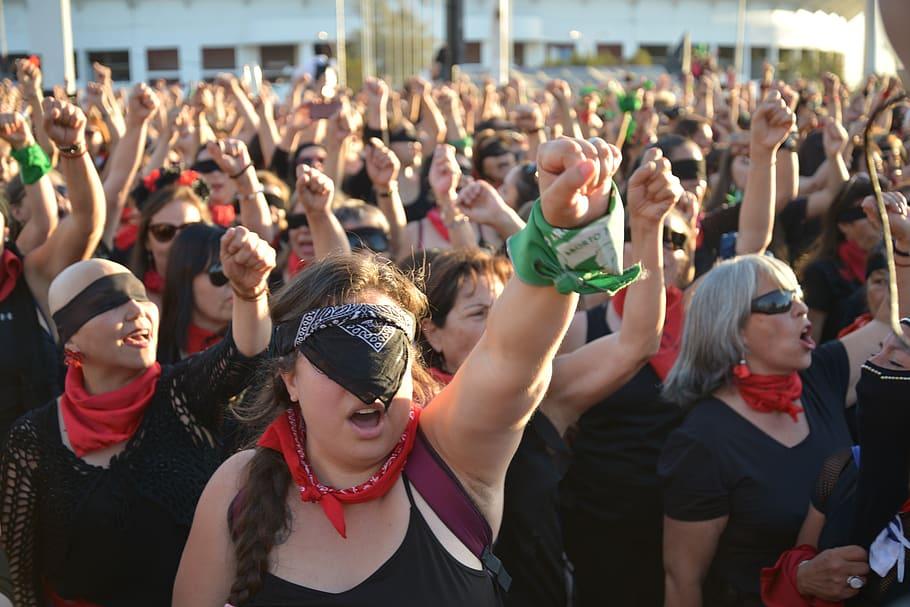 Grupo de mulheres gritando em protesto com os punhos para o alto.