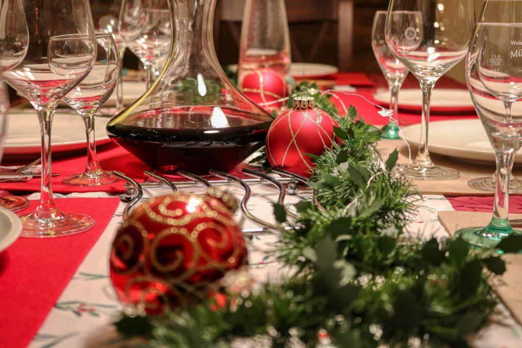 Imagem de uma linda mesa de Natal. Ela está decorada com tolhas branca e vermelha, enfeites natalinos e sobre a mesa um cantil de vidro com vinho e várias taças.