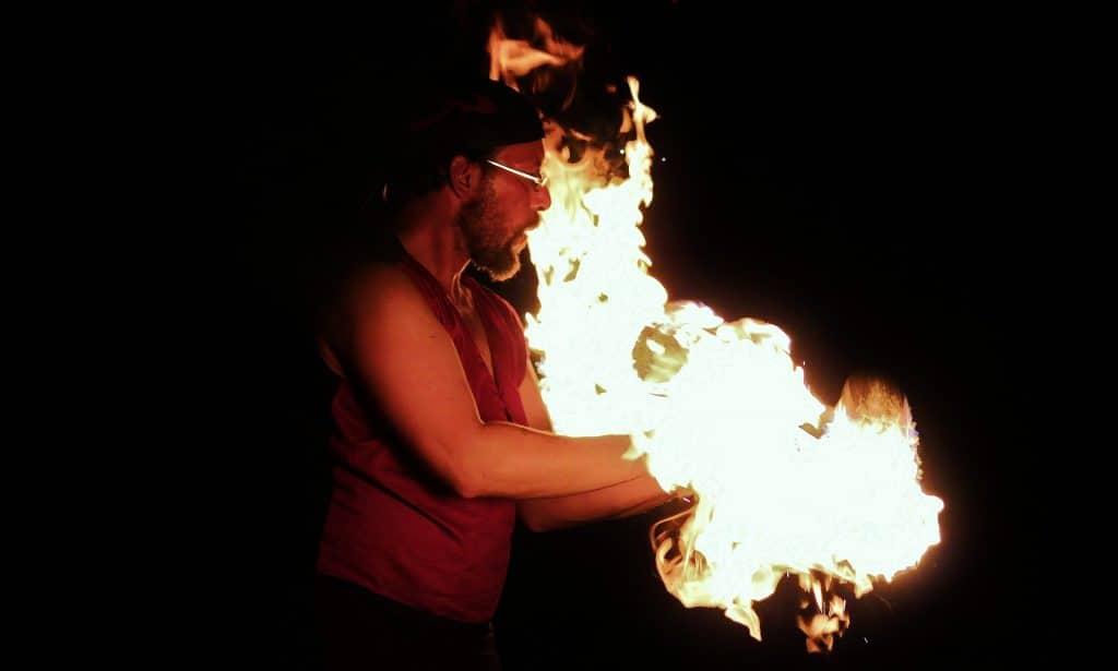 Imagem de um homem de barba e óculos usando uma camiseta regata na cor bordo. Ele está mexendo com fodo e suas mãos estão sobre o fogo.